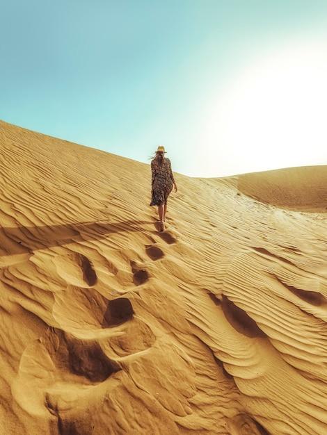 La giovane bella donna in un vestito lungo cammina lungo le dune di sabbia del deserto del dubai Foto Premium