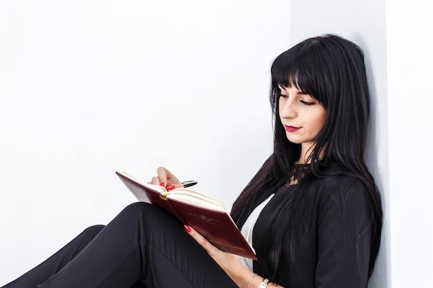 La giovane bella donna seria del brunette che si siede su un pavimento in un ufficio, scrive in un taccuino Foto Premium