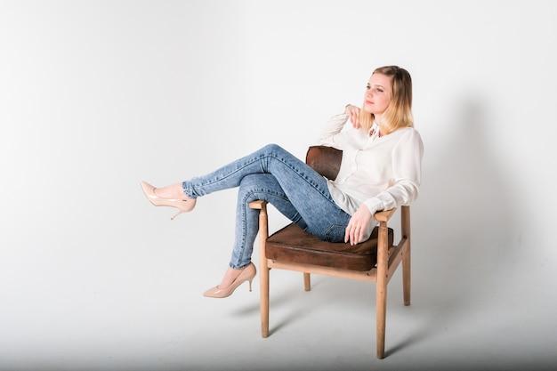 La giovane bella donna si siede su una sedia Foto Premium