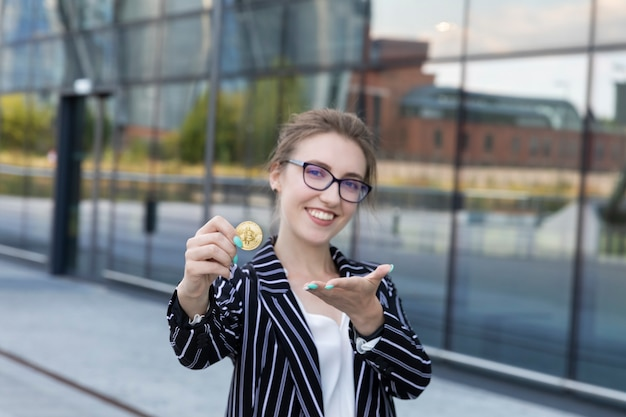 La giovane bella donna tiene bitcoin in una mano. è una donna d'affari e ha investito i suoi soldi in criptovaluta, progettando di fare buoni soldi su di essa. Foto Premium