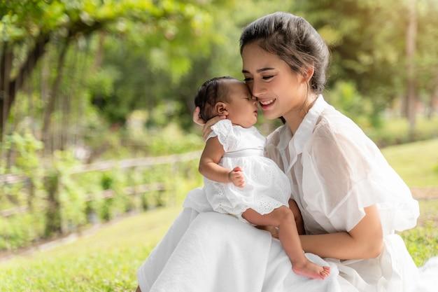 La giovane bella madre asiatica che tiene il suo neonato sta dormendo e sente con amore e toccando delicatamente quindi sedendosi sull'erba verde nel parco Foto Premium