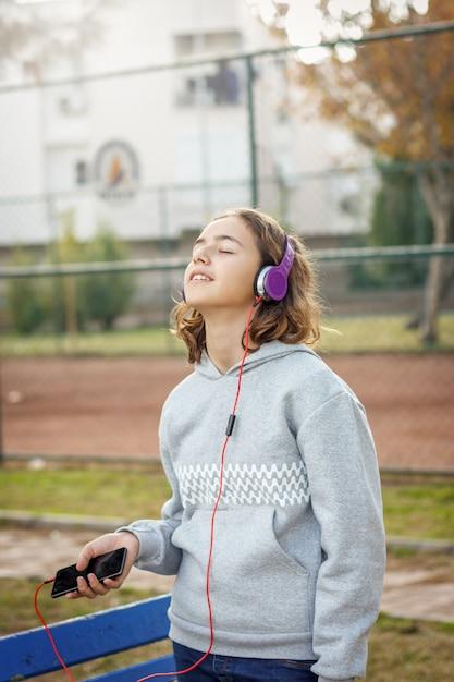 La giovane bella ragazza alla moda dell'adolescente ascolta musica sulle cuffie da uno smartphone Foto Premium