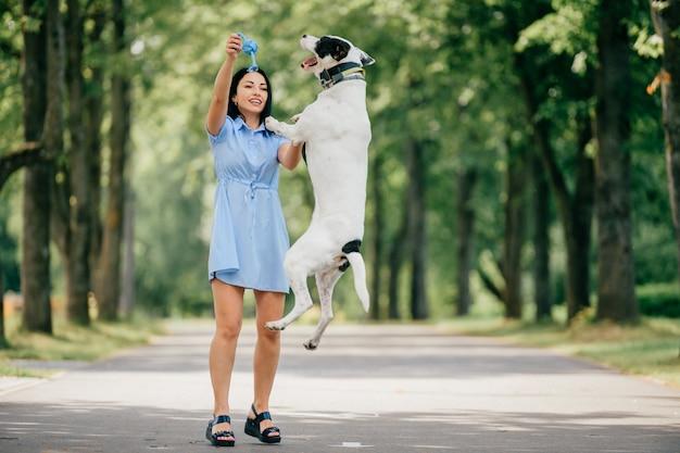 La giovane bella ragazza allegra castana in vestito blu si diverte e gioca con il suo cane bianco maschio all'aperto alla natura. la donna di bell'aspetto ama gli animali gentili Foto Premium
