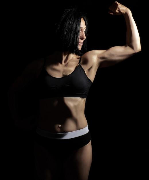 La giovane bella ragazza atletica ha sollevato e piegato il braccio dimostrando il suo bicipite Foto Premium