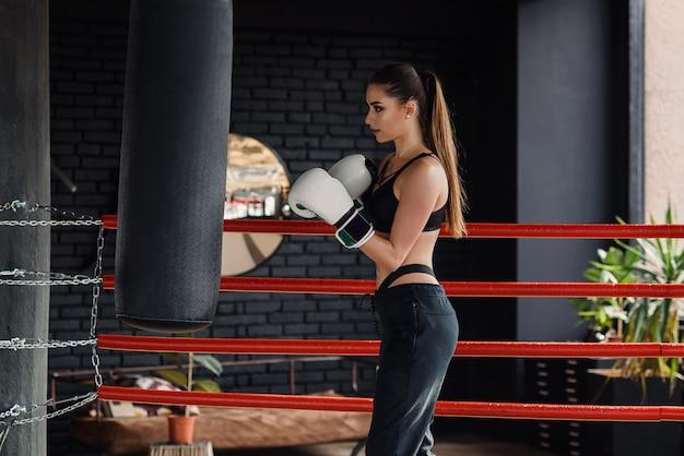 La giovane bella ragazza di sport in abiti sportivi e guantoni da pugile colpisce un punching ball in palestra nera moderna. Foto Premium