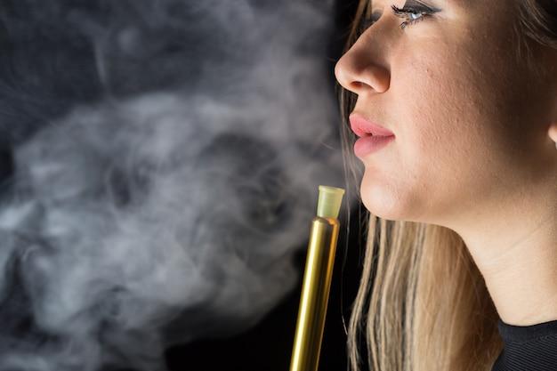 La giovane, bella ragazza fuma un narghilé Foto Premium