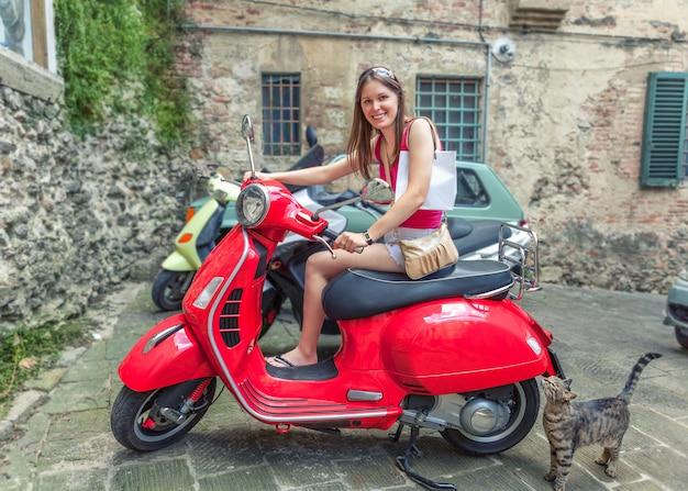 La giovane bella ragazza guida un vespa a motore rosso per le strade di roma, italia. Foto Premium