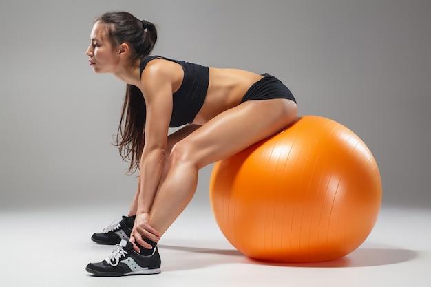 La giovane, bella ragazza sportiva che fa esercizi su fitball Foto Gratuite