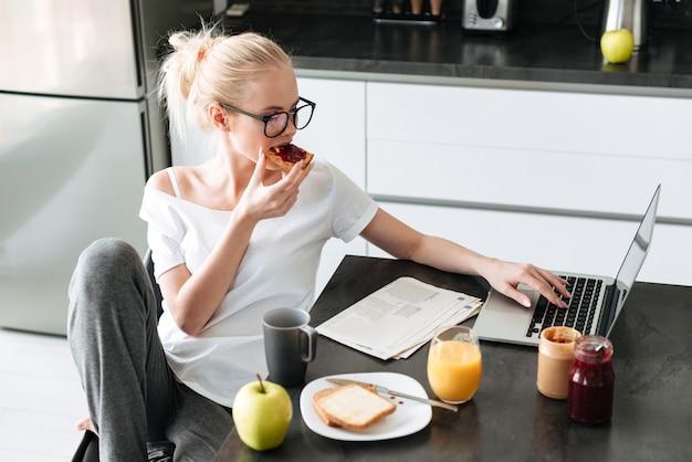 La giovane bella signora fa colazione e utilizza il computer portatile nella cucina Foto Gratuite