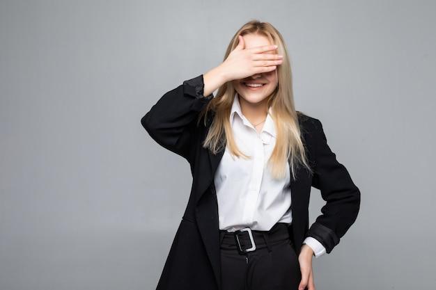 La giovane copertura della donna di affari osserva a mano sulla parete grigia isolata Foto Gratuite