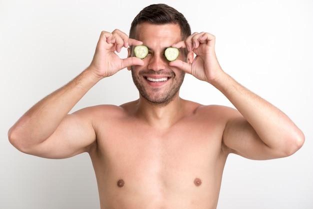 La giovane copertura sorridente senza camicia dell'uomo osserva con la fetta del cetriolo che sta contro la parete bianca Foto Gratuite