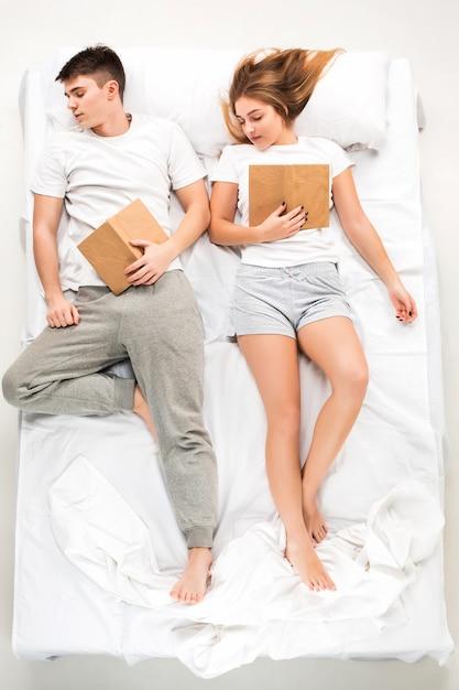 La giovane coppia adorabile che giace in un letto con i libri Foto Gratuite