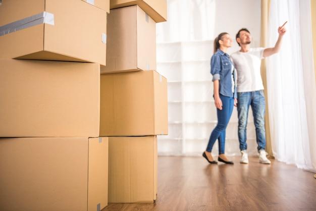 La giovane coppia felice che guarda intorno al loro nuovo appartamento. Foto Premium