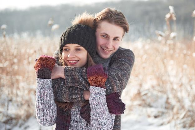 La giovane coppia felice si diverte su neve fresca alla bella giornata di sole invernale in vacanza Foto Premium