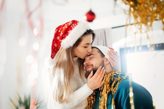 La giovane coppia in cappelli di natale decora la casa per natale e capodanno Foto Premium