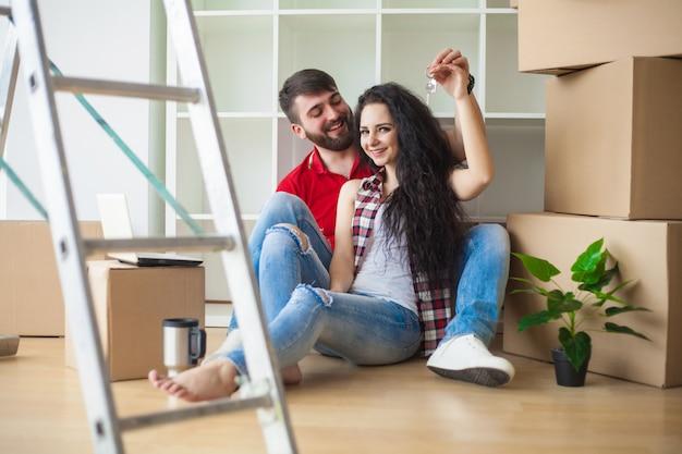 La giovane coppia mostra le chiavi al nuovo appartamento Foto Premium