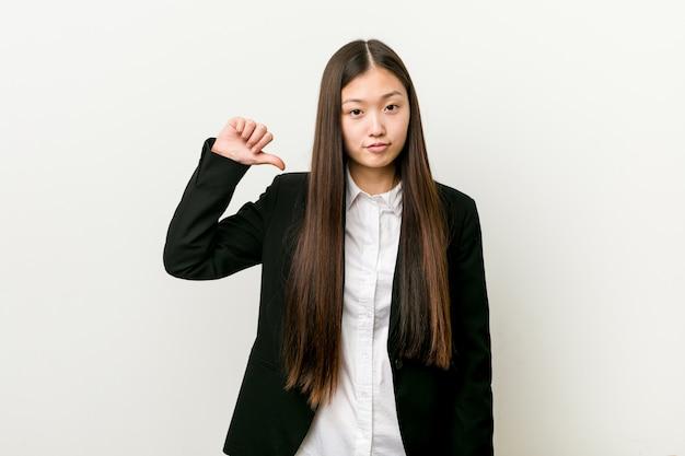 La giovane donna abbastanza cinese di affari che mostra un gesto di avversione, sfoglia giù. Foto Premium