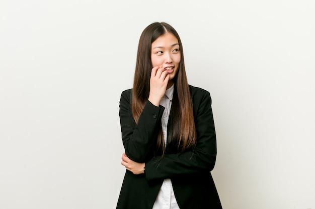 La giovane donna abbastanza cinese di affari si è distesa pensando a qualcosa che esamina uno spazio della copia. Foto Premium