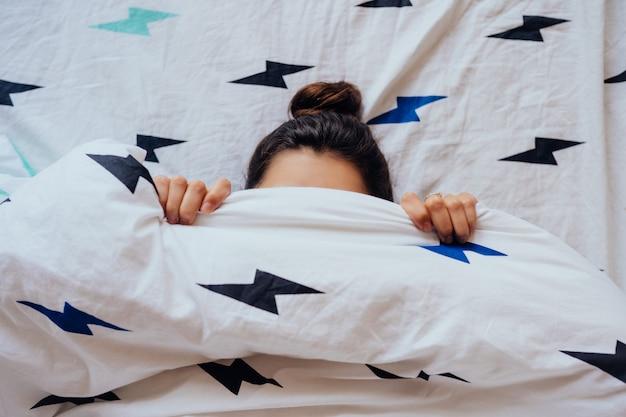 La giovane donna adorabile si trova a letto coperta di coperta Foto Gratuite