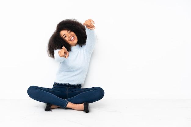 La giovane donna afroamericana che si siede sul pavimento indica il dito mentre sorride Foto Premium