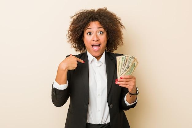 La giovane donna afroamericana che tiene i dollari ha sorpreso indicare se stesso, sorridendo ampiamente. Foto Premium