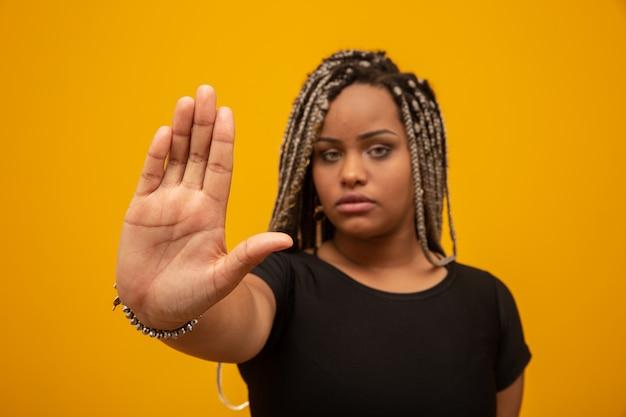 La giovane donna afroamericana ha mostrato la mano sul segno affinchè loro si fermassero con il pregiudizio razziale. Foto Premium