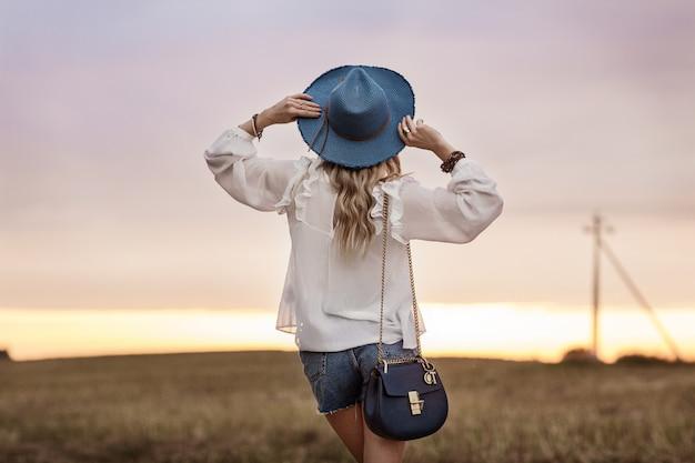 La giovane donna alla moda in un cappello esamina il tramonto Foto Premium