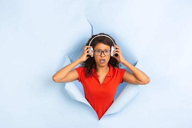 La giovane donna allegra posa nel fondo lacerato del foro della carta blu, emozionale ed espressivo Foto Gratuite