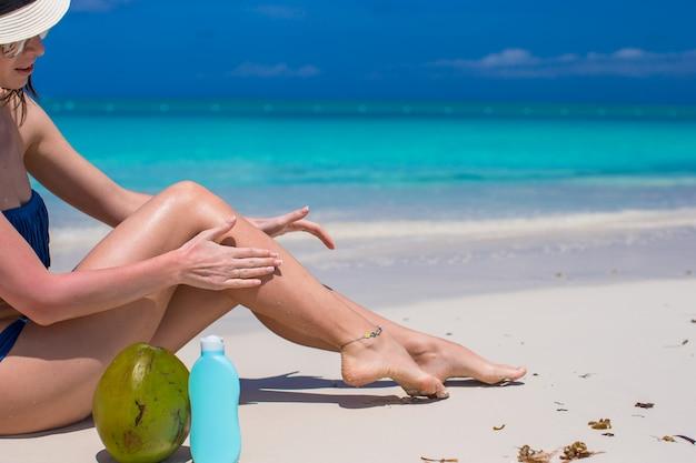La giovane donna applica la crema sulle sue gambe abbronzate lisce alla spiaggia Foto Premium