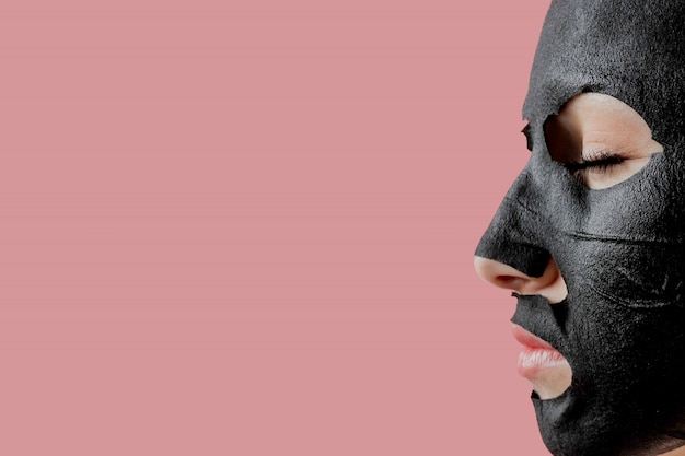 La giovane donna applica la maschera facciale nera del tessuto cosmetico su fondo rosa. maschera peeling viso con carbone, trattamenti di bellezza spa, cura della pelle, cosmetologia. avvicinamento Foto Premium