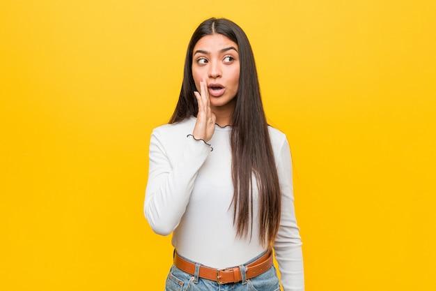 La giovane donna araba graziosa contro un giallo sta dicendo una notizia di frenata calda segreta e sta guardando da parte Foto Premium