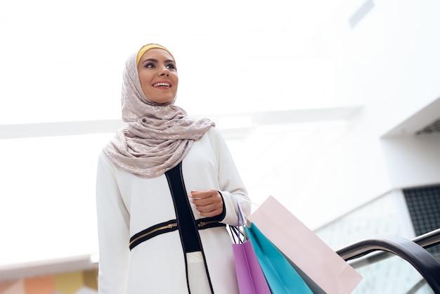 La giovane donna araba sta stando vicino alla scala mobile. Foto Premium