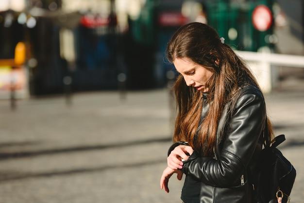 La giovane donna arriva in ritardo per un appuntamento, mentre aspetta in strada. Foto Premium