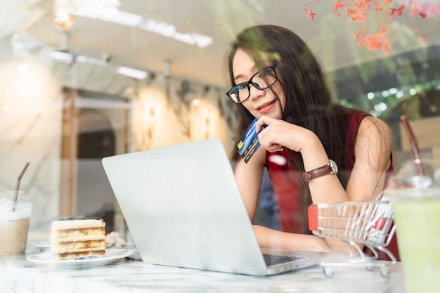 La giovane donna asiatica attraente che utilizza la carta di credito che effettua il pagamento online e le attività bancarie di internet sul computer portatile mentre si siede si rilassa nella caffetteria Foto Premium