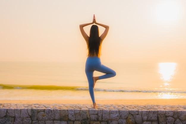 La giovane donna asiatica del ritratto fa la meditazione intorno all'oceano della spiaggia del mare all'alba Foto Gratuite