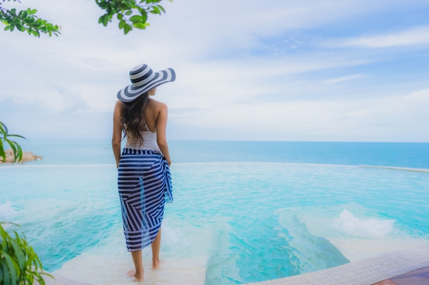 La giovane donna asiatica del ritratto si rilassa il sorriso felice intorno alla piscina all'aperto nella località di soggiorno dell'hotel con la vista di oceano del mare Foto Gratuite