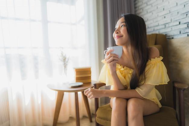 La giovane donna asiatica del ritratto si siede sulla sedia del sofà e legge il libro con la tazza di caffè Foto Gratuite