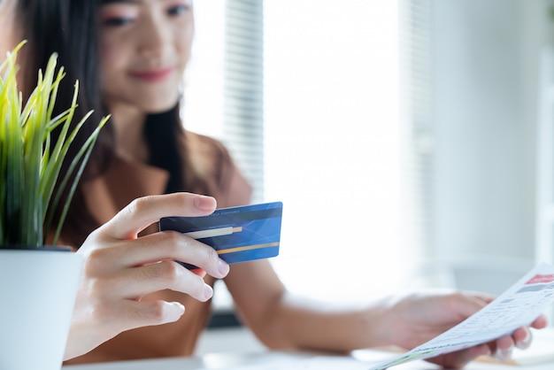 La giovane donna asiatica felice che sorride con la vita facile per paga le sue spese mensili fatture dalla carta di credito Foto Premium