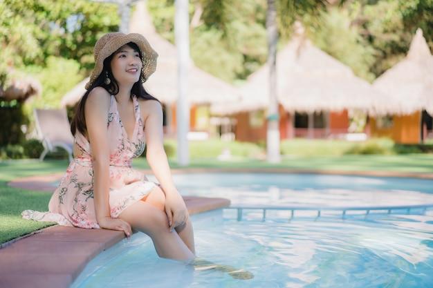 La giovane donna asiatica si rilassa vicino alla piscina in hotel, bella femmina felice si rilassa vicino al mare. Foto Gratuite