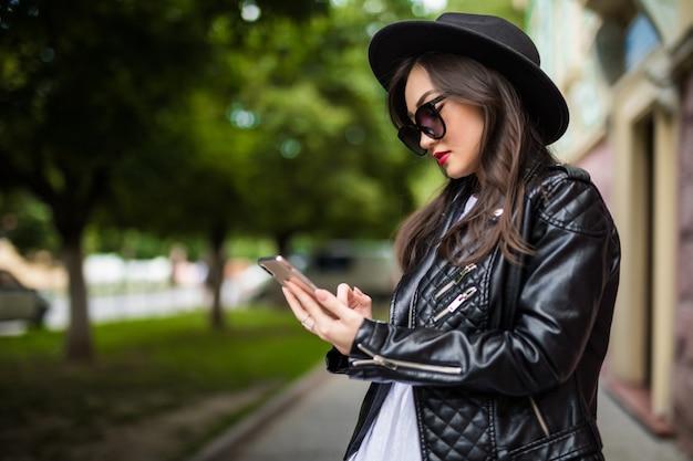 La giovane donna asiatica utilizza lo smart phone sulla via Foto Gratuite