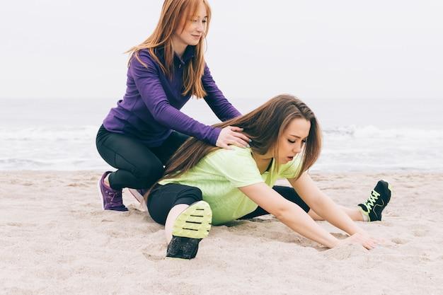 La giovane donna atletica che fa gli sport si esercita sulla spiaggia in tempo nuvoloso Foto Premium