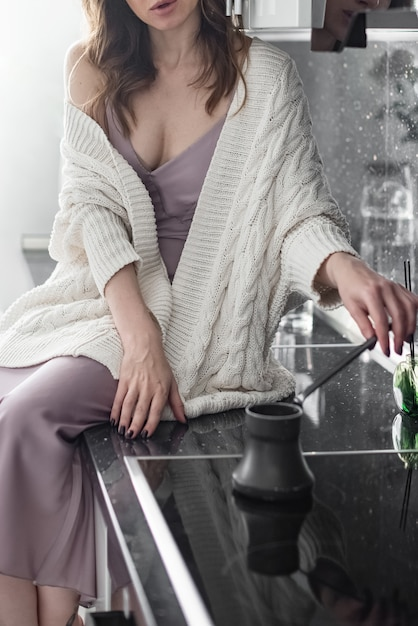 La giovane donna attraente che porta il maglione bianco tricottato si siede sul ripiano del tavolo della cucina che produce il caffè preparato di mattina Foto Premium