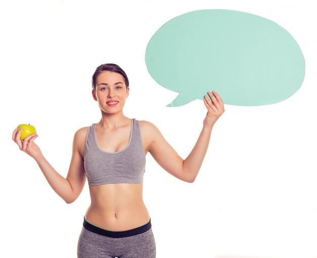 La giovane donna attraente in abiti sportivi sta sorridendo. Foto Premium