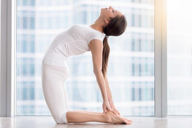 La giovane donna attraente in ustrasana posa contro il pavimento Foto Gratuite