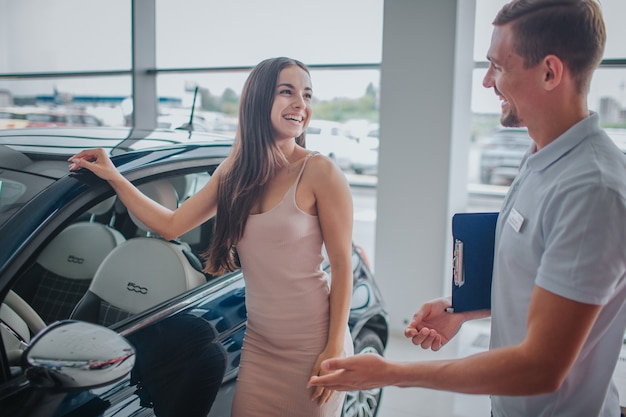 La giovane donna bella e positiva sta oltre all'automobile nera e la tiene su. guarda l'addetto alle vendite e sorride. i giovani la guardano e sorridono anche loro. indica in macchina. Foto Premium