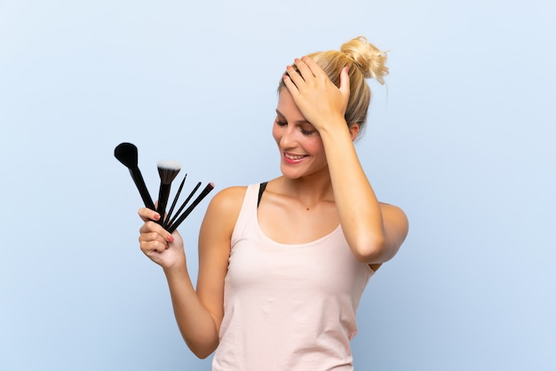 La giovane donna bionda che detiene un sacco di pennello per il trucco ha realizzato qualcosa e intendendo la soluzione Foto Premium