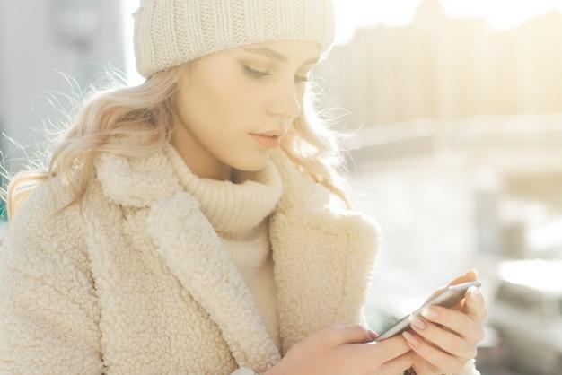 La giovane donna bionda in vestiti dell'inverno esamina lo smartphone e sorridere. Foto Premium