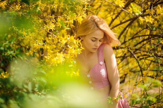 La giovane donna bionda si è vestita in un vestito rosa che sta vicino all'albero di fioritura giallo Foto Premium