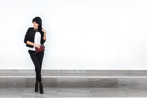 La giovane donna castana seria attraente con un taccuino si è vestita in un vestito nero che sta contro la parete bianca in un ufficio. Foto Premium