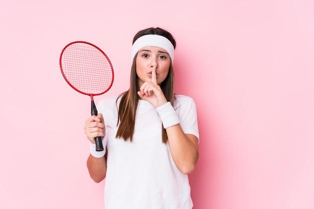 La giovane donna caucasica che gioca il volano ha isolato mantenendo un segreto o chiedendo il silenzio. Foto Premium
